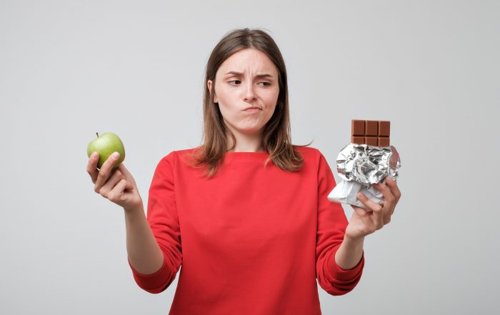 Woman holding a green apple and a chocolate. Concept of healthy diet