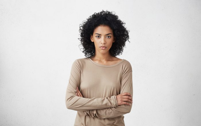 Indoor shot of angry agrumpy young mixed race female dressed casually keeping arms folded, looking at camera with strict and skeptical expression, doesn't believe excuses of her unfaithful boyfriend