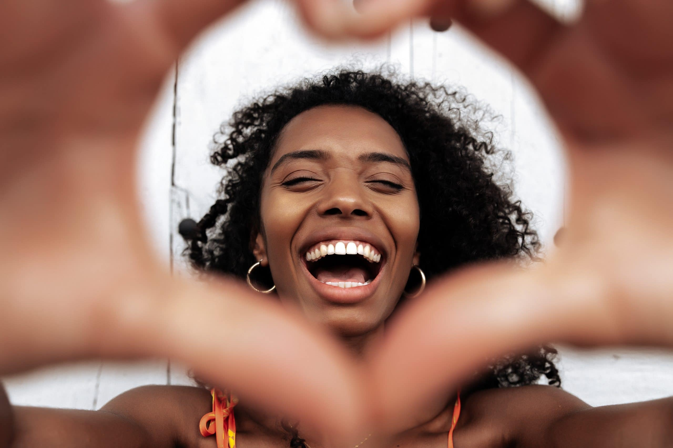 Optimistic young African American female laughing happily and showing heart shaped sign while standing against old wall