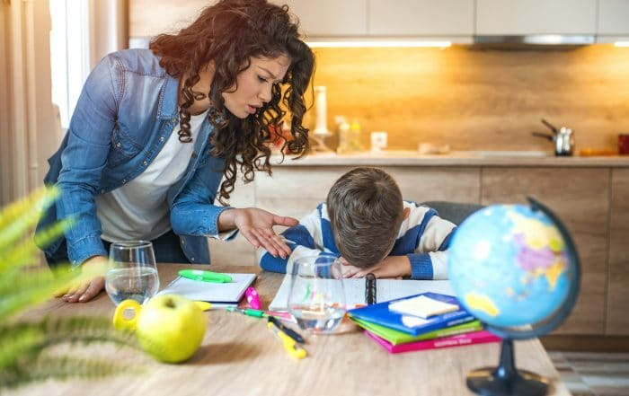 Frustrated mom doing homework with son. The son's head in down on top of his homework